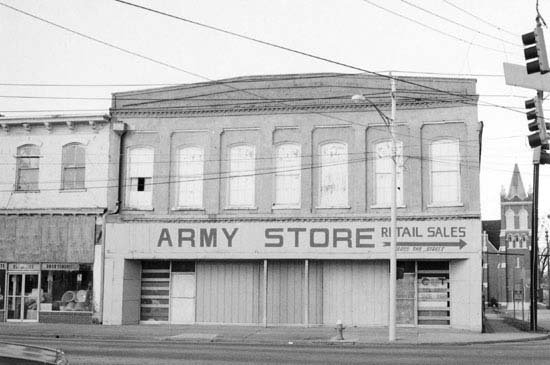 Black and white photograph of old two story building with boarded windows