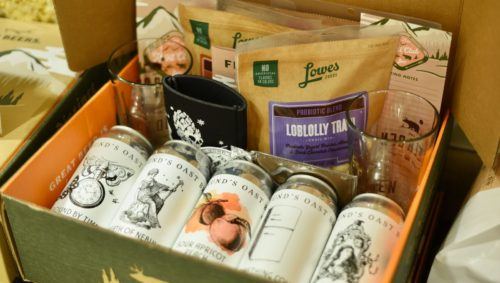 Photo of a Lowes Foods beer hunting box, showing Loblolly trail mix, a koozie, two drink glasses, and five canned beers.