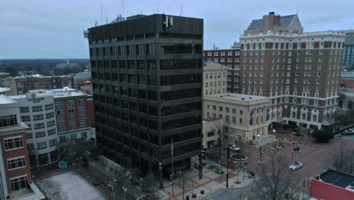 Aerial shot of current city hall building (tall, multi-story, black mid-century building)
