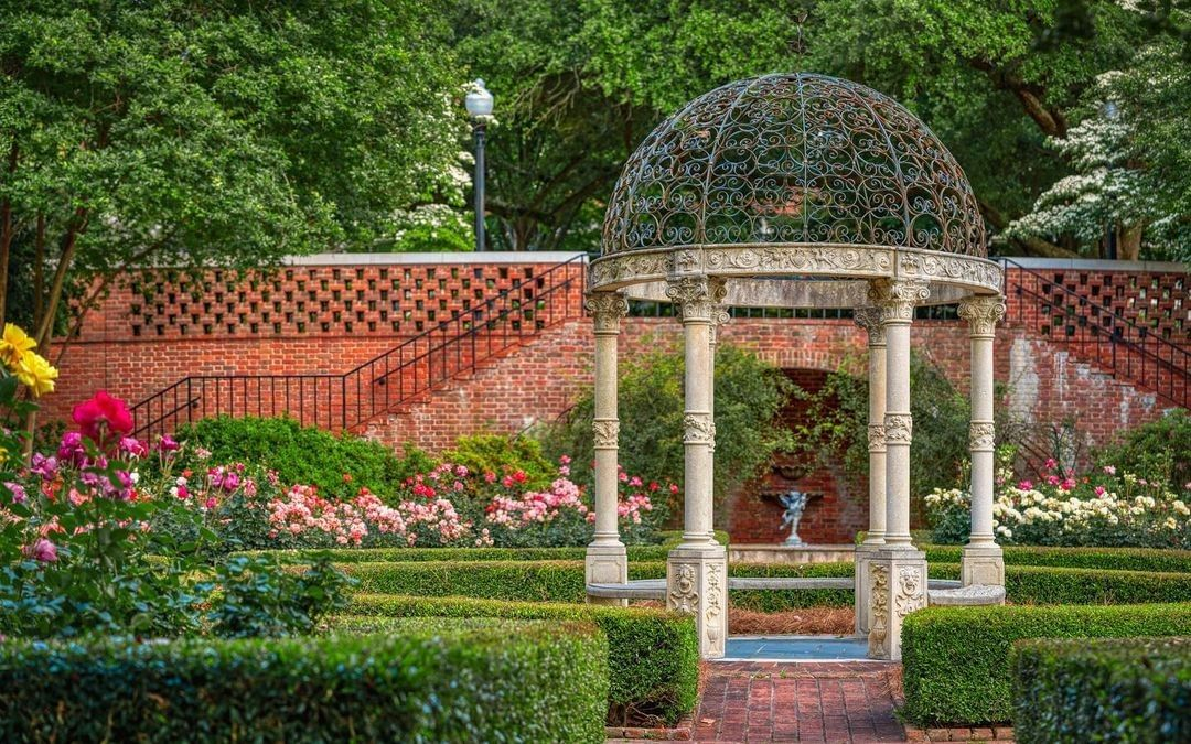Gazebo with decorative iron cover surrounded by colorful roses and boxwood hedges