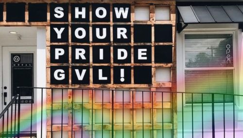 """White building white black letters spelling """"Show your pride, GVL"""" with a rainbow overlay"""