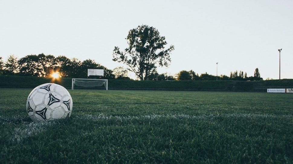 Soccer ball on soccer field with goal and sunset in the background