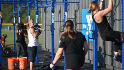 Women working out with weights and pull up bars in outside gym area